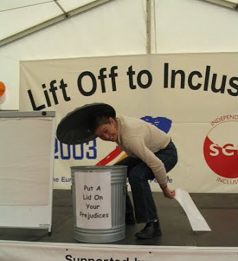 Lift Off to Inclusion campaign poster showing a woman with a dustbin saying put your prejudice in here