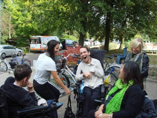 Photo of a group of Disabled People and a Personal Assistant outdoors sitting in the park