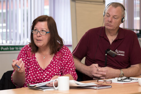 Photo of a volunteer supporting someone at a meeting by taking notes for them
