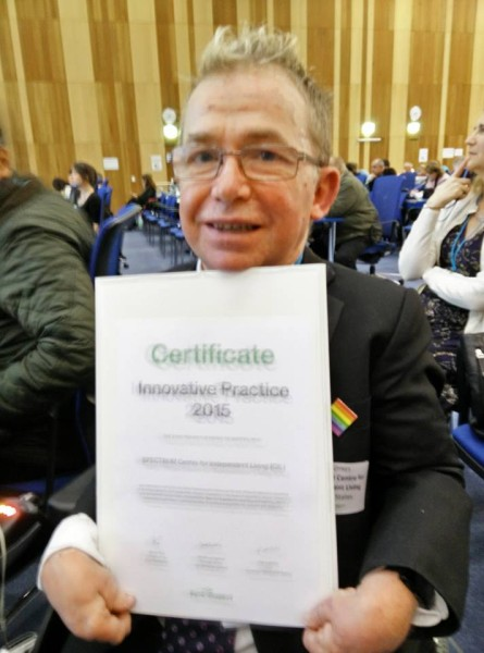 Our Chief Executive holding our Zero Project award certificate in Vienna