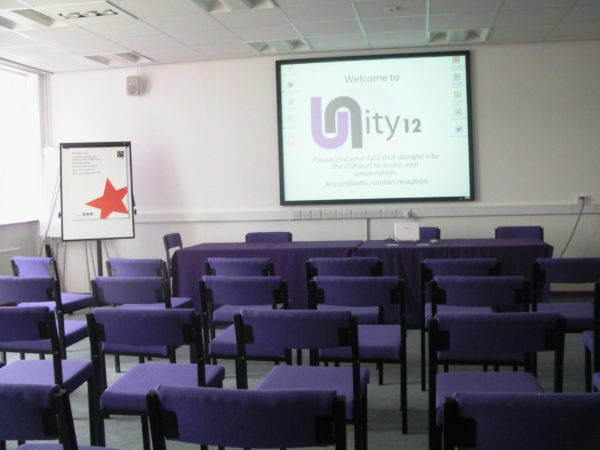 Rows of empty chairs and a display screen in the Unity 12 Conference Centre
