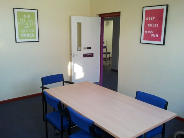 A desk and 4 chairs in a small meeting room with door opening onto corridor